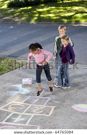 Asian girl jumping on hopscotch board with friends watching.  Girls 7 years, boy 9. - stock photo
