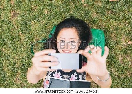 Asian Girl Laying Down on the Grass and Taking Selfie - stock photo