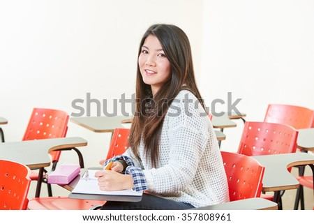 Asian girl learning in her classroom at school - stock photo
