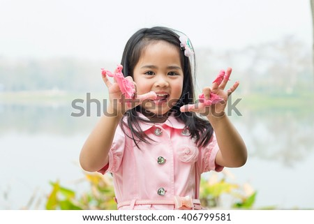 Asian girl learning to use playing clay in the park.
