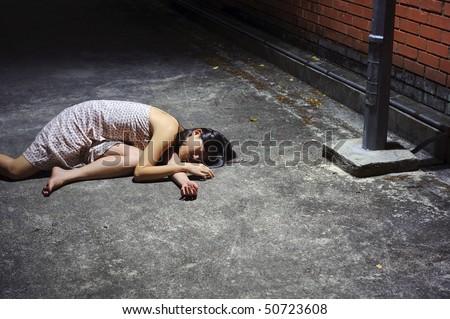 Asian girl lies in an empty street - stock photo
