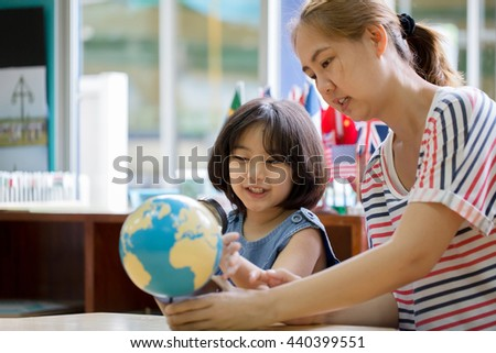 Asian girl looking at globe while listening to teacher with magnifying glass - stock photo
