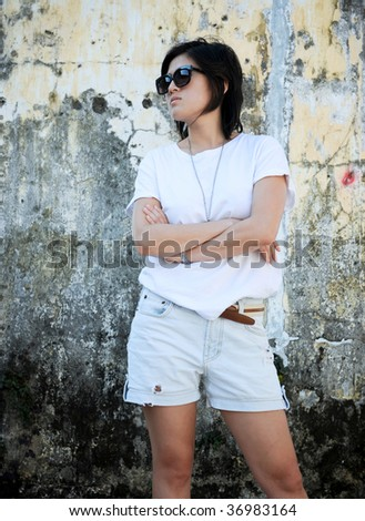 Asian girl looks away and folds her arms - stock photo