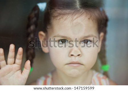 Asian girl misses at the window - stock photo
