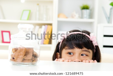 Asian girl peeking over table at cookies inside the glass bottle