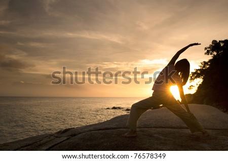 asian girl performing yoga on beach, warrior pose - stock photo