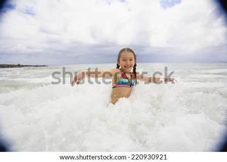 Asian girl playing in surf