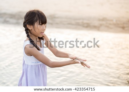 Asian girl playing on the beach with sun light. - stock photo