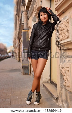 Asian girl posing near wall on street