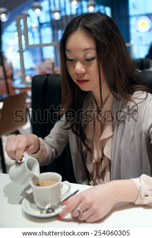 Asian girl pours cream into coffee - stock photo