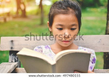 Asian girl reading a book on park in free time. Soft focus