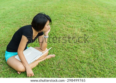 Asian girl rest her eyes after she use laptop in garden, young woman sit and relax on green grass - stock photo
