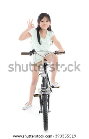 Asian girl riding a bike and showing thumb on white background isolated - stock photo
