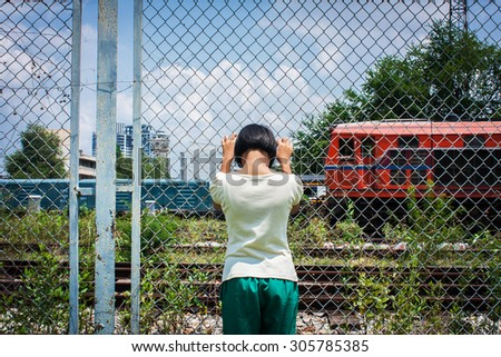 asian girl sad alone hand hold jail at Railroad,railway station - stock photo