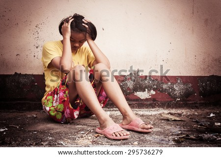 asian girl sad alone sitting with white bear near old wall cement,vintage tone - stock photo