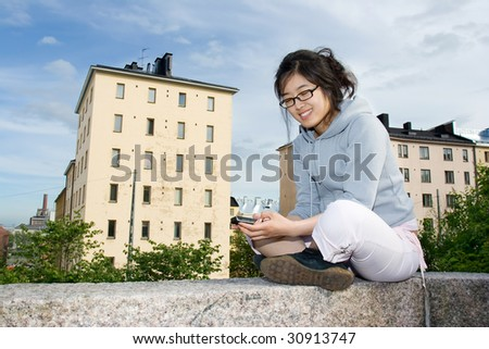 Asian girl sending a sms message - stock photo