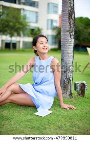 Asian girl sitting on grass reading