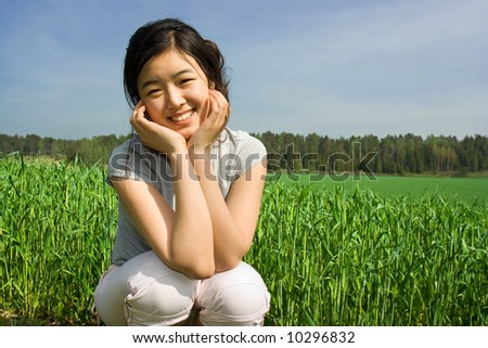 Asian girl smiling on a field - stock photo
