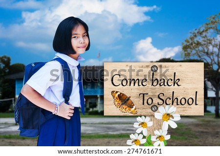 asian girl student wear uniform Thai gesturing in front of the school building with signpost in beautiful come back to school - stock photo