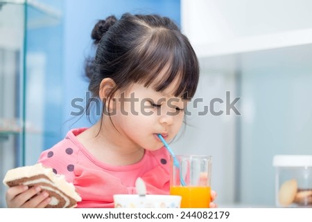 Asian girl sucking juice from a glass in one hand and bread.