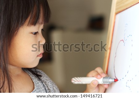 Asian girl tracing a drawing with marker pen on a drawing board - stock photo