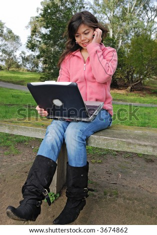Asian girl using laptop and phone outdoors - stock photo