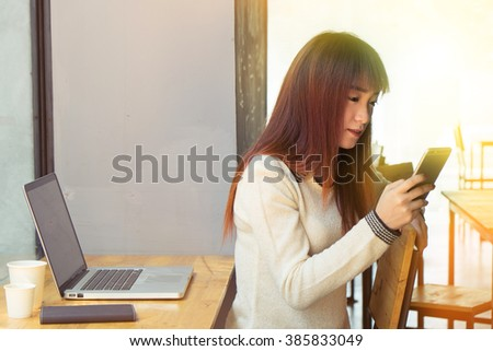 Asian girl using smartphone in cafe or co-working with morning light.