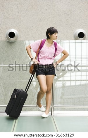 asian girl waiting at singapore's changi airport terminal