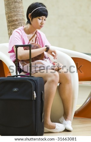 asian girl waiting at the airport terminal impatiently - stock photo