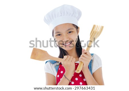Asian girl wearing apron and holding cooking utensils - stock photo