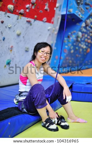 Asian girl wearing harness and belaying rope, ready to do rock climbing. - stock photo