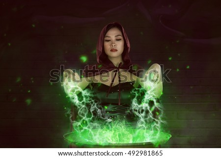 Asian girl witch with red cloak preparing a magic potion in the cauldron