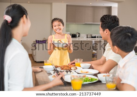 Asian girl with a bowl of salad standing in front of family dinner table - stock photo