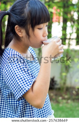 Asian girl with a glass of chocolate milk - stock photo