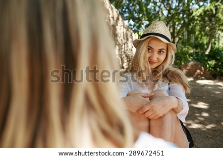 Asian girl with friend summer portrait in park. Smiling happy mixed race Asian Caucasian woman in 20s looking at her friend. - stock photo