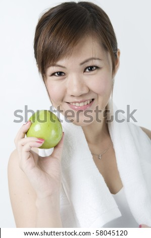 asian girl with green apple after exercising - stock photo