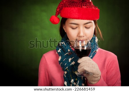 Asian girl with red christmas hat drink red wine on dark green background