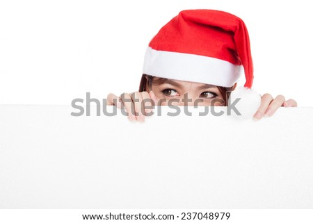 Asian girl with red santa hat peeking behind a blank board  isolated on white background - stock photo