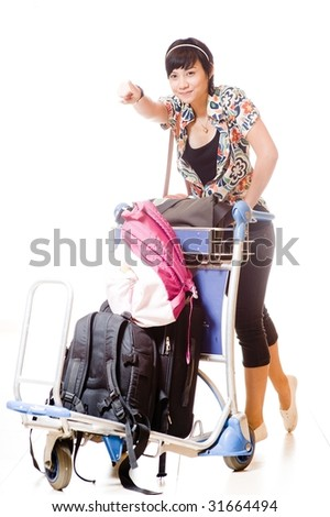 asian girl with trolley loaded with luggage and bags on white background and tiled floor - stock photo