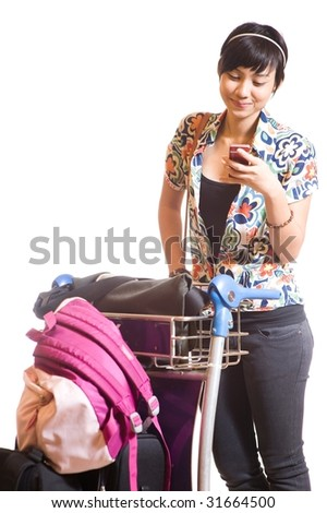asian girl with trolley loaded with luggage and bags using mobile phone - stock photo