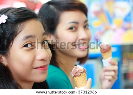 asian girls enjoying ice cream - stock photo