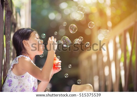 asian girls play blowing bubbles on a bridge in the forest.