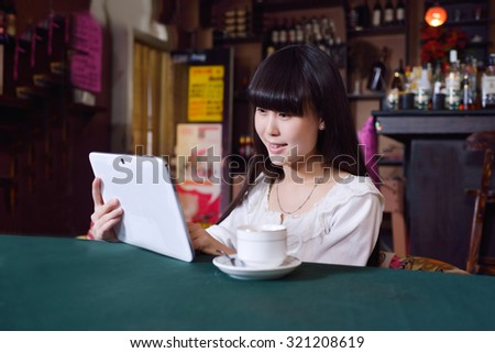Asian girls using Tablet PC at a coffee shop. - stock photo