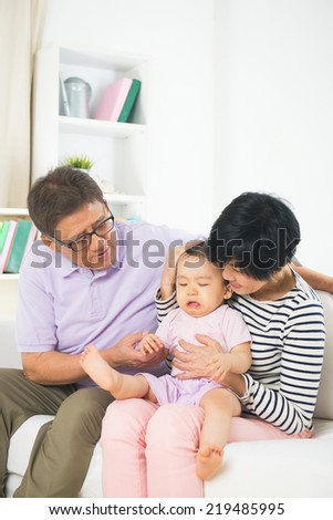 asian grand parents comforting their spoilt crying granddaugther