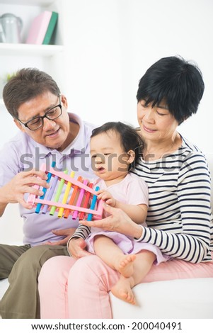 asian grand parents teaching granddaughter music lesson - stock photo