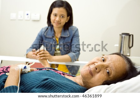 asian granddaughter visit her sick grandmother having bed resting in inpatient treatment at the hospital - stock photo