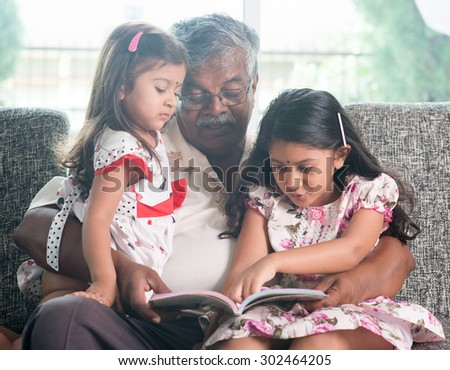 Asian grandfather and granddaughters reading story book. Happy Indian family at home. Grandparent and grandchildren indoor lifestyle.