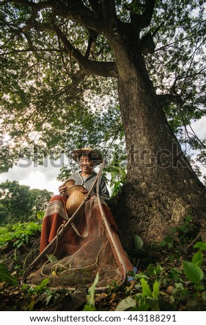 Asian grandmother fisherman with the net bamboo under the big tree