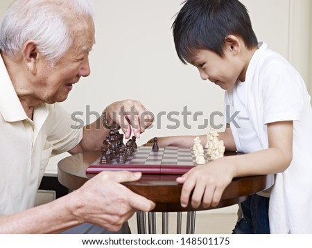 asian grandpa and grandson playing chess.