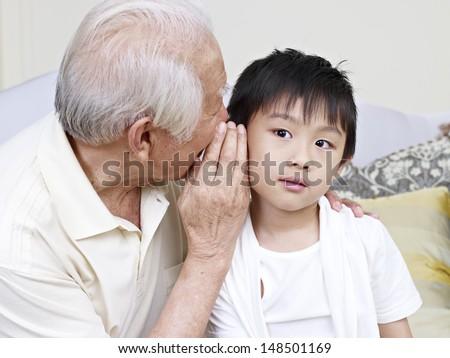 asian grandpa telling grandson a secret. - stock photo